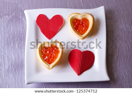 Tartlets with red caviar and paper hearts on Valentine's Day
