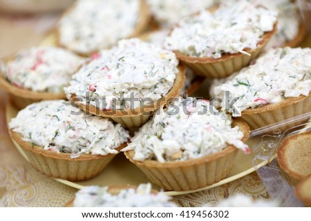 Tartlets with salad on yellow plate at picnic