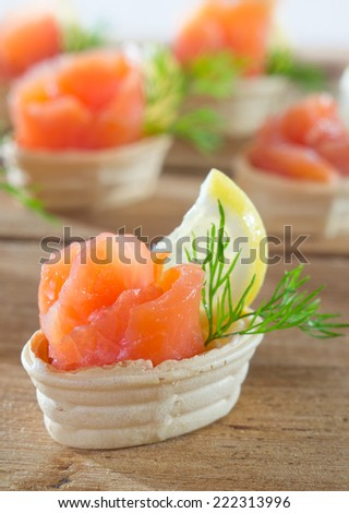 Tartlets with salmon, lemon and decorated with dill. - stock photo