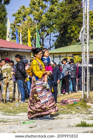 TASHIDING, INDIA - MARCH 16, 2014:A woman at the bumchu festival, Tashiding, Sikkim. In the background buddhist believers, men and women, are queuing in two lines to get into the temple. - stock photo