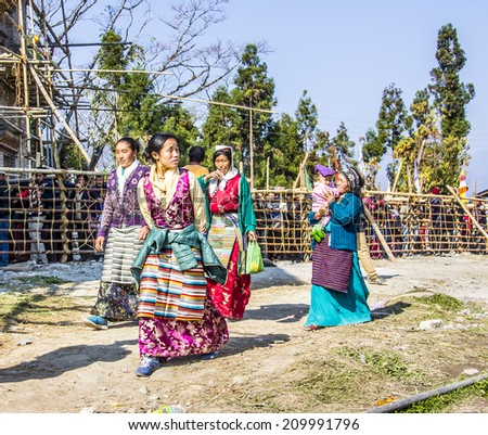 TASHIDING, INDIA - MARCH 16, 2014: Four women at the bumchu festival, Tashiding, Sikkim. In the background buddhist believers, men and women, are queuing in two lines to get into the temple. - stock photo