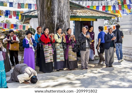 TASHIDING, INDIA - MARCH 16, 2014: Tibetan men and women, the women in traditional costume, at the bumchu festival, Tashiding, Sikkim, are worshipping the buddha. - stock photo