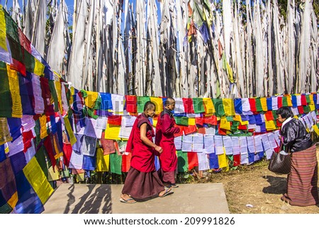 TASHIDING, INDIA - MARCH 16, 2014: Two buddhist monchs at the bumchu festival, Tashiding, Sikkim. A woman bows respectfully. In the background are lots of prayer flags. - stock photo