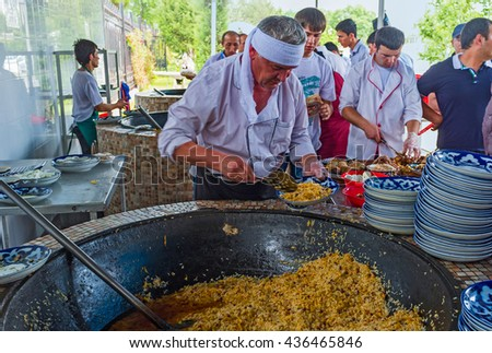 TASHKENT, UZBEKISTAN - MAY 7, 2015: The chef puts the pilaf from a cauldron (qozon) to the plates in open air kitchen of Center Asian Plov Center, on May 7 in Tashkent. - stock photo