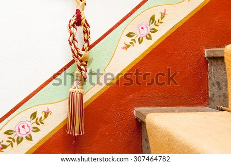 Tassel on red diagonal design, indoor house decoration - stock photo