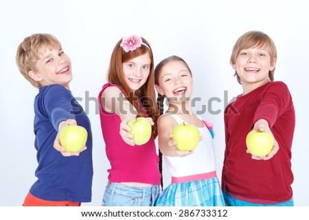Taste it. Little upbeat friends standing together and holding fresh apples while smiling.