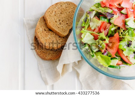 taste of vegetarian summer concept, salad of lettuce leaf, tomato, cucumber, onion, oregano with olive oil and lemon juice on white wooden background