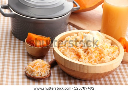 Taste rice porridge with pumpkin and glass of juice on tablecloth background