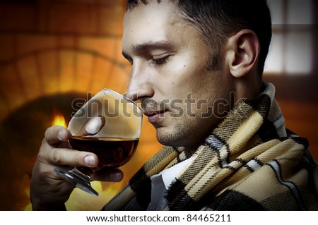 Taster. Young adult Man in tartan plaid holding in hand a glass of classy extra old brandy or cognac and smell it. He is inside home room siting about fireplace - stock photo