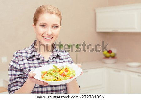 Tastes delicious. Portrait of a happy young woman holding plate with fresh salad in her hands and offering it to you - stock photo