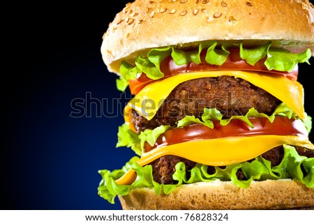 Tasty and appetizing hamburger on a dark blue background - stock photo