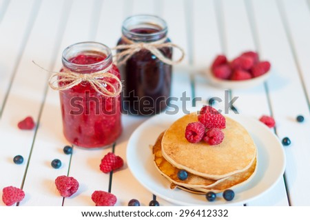 Tasty and beautiful food. Pancake with berries jam or marmalade in mason jar. - stock photo