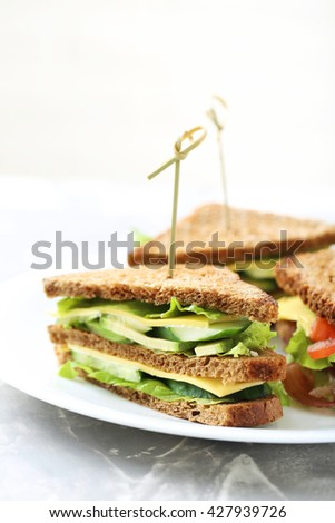 Tasty and fresh sandwiches on a grey table - stock photo