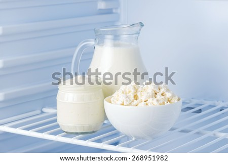 tasty and healthy dairy products in the refrigerator: sour cream, cottage cheese and milk - stock photo