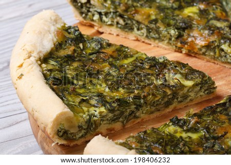 tasty and healthy vegetable pie with spinach macro on a cutting board.  - stock photo