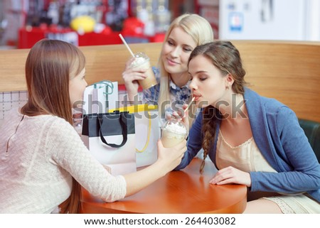 Tasty and sweet cocktails after the shopping. Three beautiful young shopping women having milk cocktails in the shopping mall - stock photo