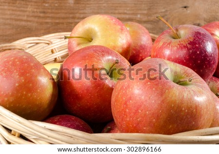 Tasty apples in a basket on wooden background - stock photo