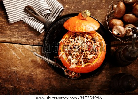 Tasty autumn stuffed pumpkin with fresh mushrooms ready to serve for a seasonal dinner, overhead view on rustic wooden table with copyspace - stock photo