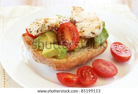 Tasty avocado, baby tomato and grilled chicken bruschetta on ciabatta bread - stock photo