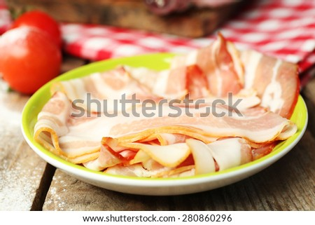 Tasty bacon on plate on table close up - stock photo