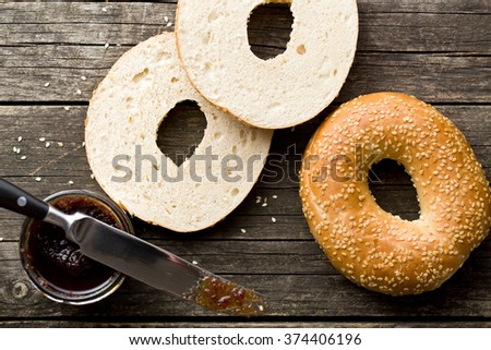 tasty bagel with sesame seed on old wooden table - stock photo