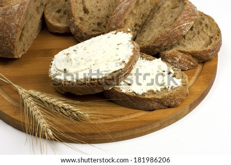 Tasty baguette  with cheese cream on a wooden board - stock photo