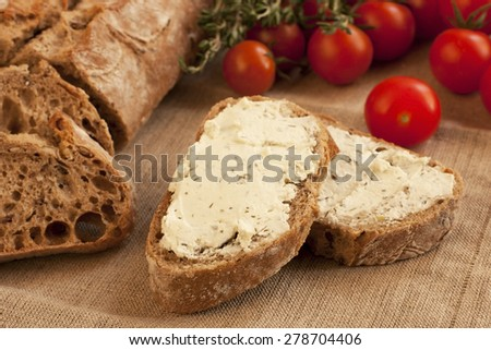 Tasty baguette  with cheese cream  on burlap - stock photo