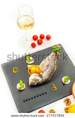 Tasty baked fish on table with wine close-up - stock photo
