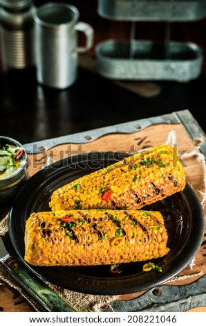 Tasty barbecued corn on the cob seasoned with butter, herbs and spices on a plate in a rustic kitchen or tavern for a tasty lunch - stock photo