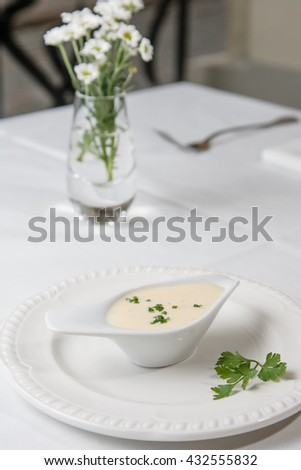 Tasty Bechamel sauce or white sauce with fresh greenery