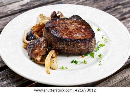 Tasty Beef Mignon steak with mushrooms and herbs on plate. - stock photo