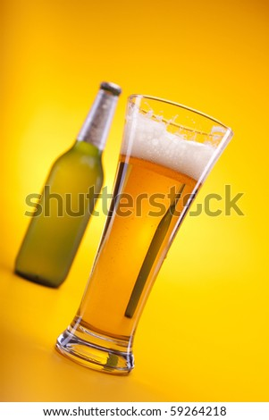 Tasty beer shot in studio with bottles and mug, golden pure beer!