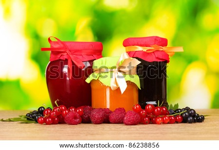 tasty berry and fruit jam and berry on a green background - stock photo