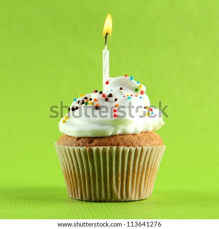 tasty birthday cupcake with candle, on green background - stock photo