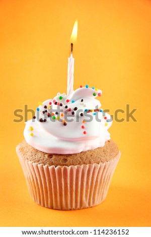 tasty birthday cupcake with candle, on orange background - stock photo