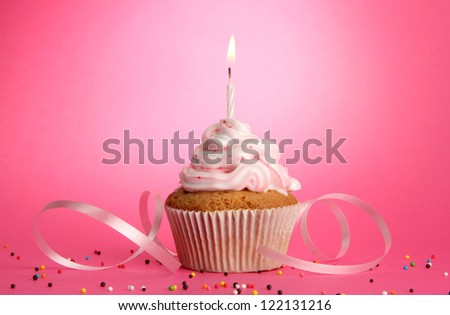 tasty birthday cupcake with candle, on pink background - stock photo
