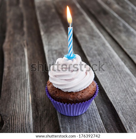 Tasty birthday cupcake with candle on wooden table - stock photo