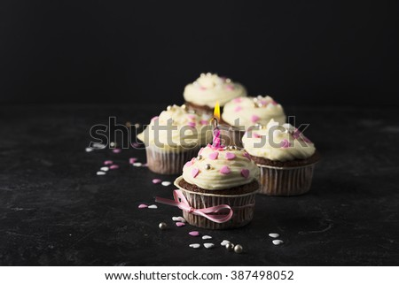 Tasty birthday cupcakes wiith candle, on black background. Toned for art effect. - stock photo