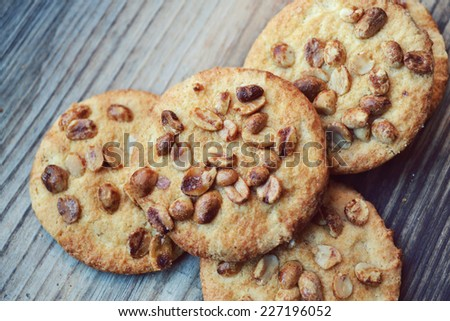 Tasty biscuits with candied peanuts on wooden table
