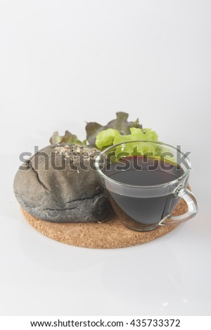Tasty black hamburgers with salad and cup of black strong coffee, on white background.