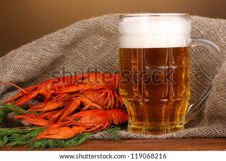 Tasty boiled crayfishes and beer on table on brown background