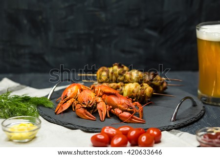 Tasty boiled crayfishes, barbecue and beer on wooden table with vegetables and sauce. Concept snacks - stock photo