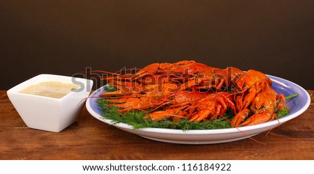 Tasty boiled crayfishes with fennel on table on brown background - stock photo