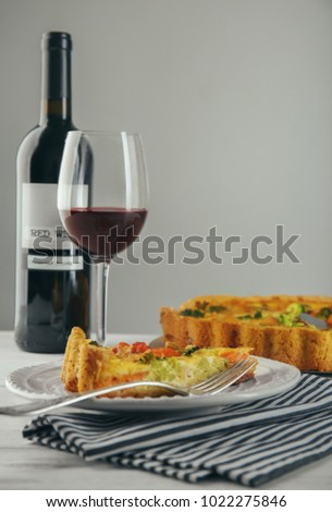 Tasty broccoli quiche served with wine on table