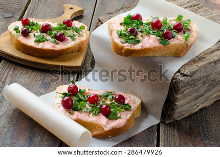 Tasty bruschetta with salmon butter, capelin caviar, cranberry and herbs on a thick wooden board, paper, rustic - stock photo