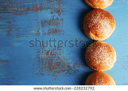 Tasty buns with sesame on color wooden background - stock photo