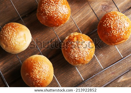 Tasty buns with sesame on oven-tray, on wooden background - stock photo