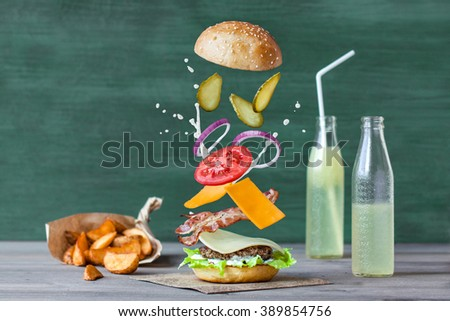 Tasty burger with juicy beef, salad, two type of cheddar cheese, bacon, sliced tomato, onion and cucumbers with ranch dressing and homemade bun with sesame seeds. French fries and lemonade - stock photo