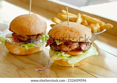 Tasty burger with melted cheese and a thick succulent ground beef patty garnished with lettuce, tomato, onion and rocket on a sesame bun standing on a table - stock photo