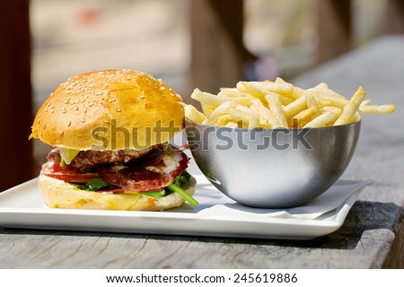 Tasty burger with melted cheese and a thick succulent ground beef patty garnished with lettuce, tomato, onion and rocket on a sesame bun standing on a table with french fries - stock photo